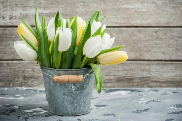 Tulipes blanches et jaunes dans un seau en étain
