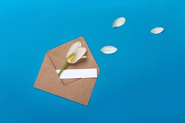 Tulipes blanches avec des pétales, une note d'amour et une enveloppe sur un fond bleu
