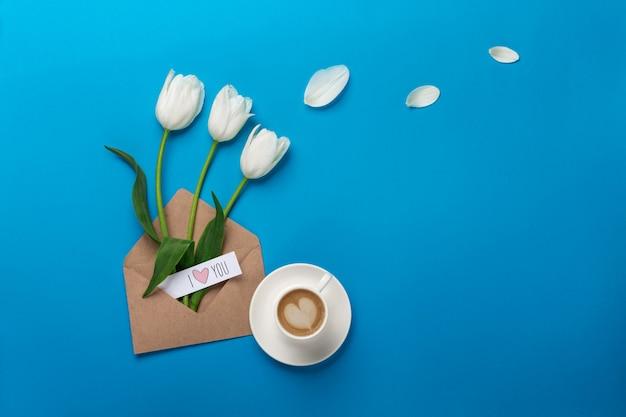 Tulipes blanches avec des pétales, une tasse de café, une note d'amour et une enveloppe sur un fond bleu