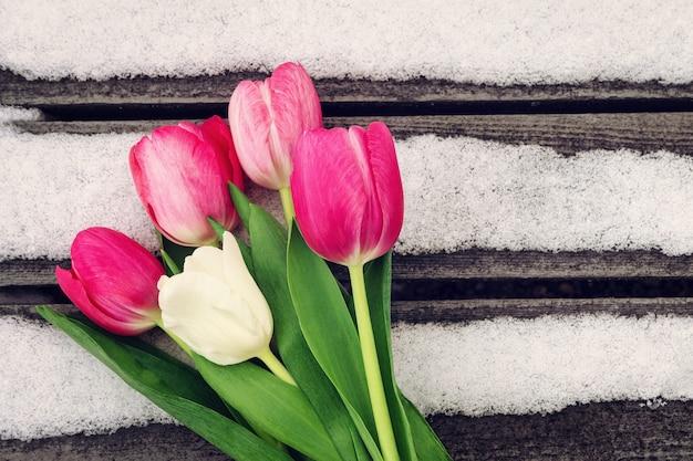 Tulipes blanches et roses sur fond de bois avec de la neige avec espace de copie pour la conception