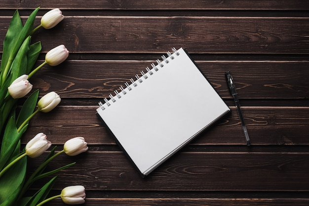 Tulipes blanches sur une table en bois avec un cahier vide. lay plat, composition vue de dessus