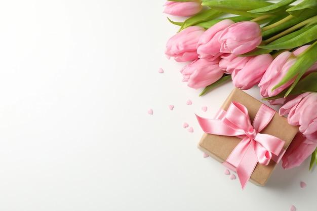 Tulipes, cadeaux et coeurs sur blanc, espace pour le texte