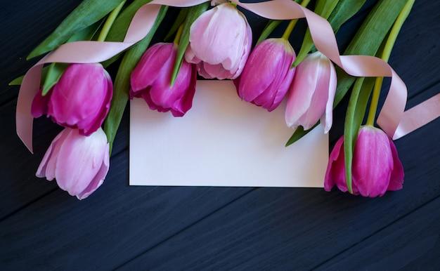 Tulipes avec carte blanche sur un bois