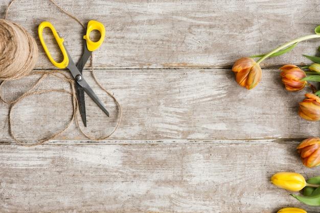 Tulipes, ciseaux et corde sur fond en bois. vue de dessus sur le lieu de travail avec des outils de bricolage et des fleurs. matériel de décoration, fleuriste, décorateur, concept fait main.