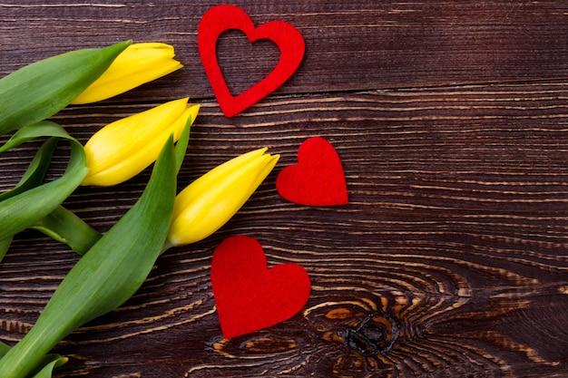 Tulipes et coeurs sur bois. fleurs jaunes près des coeurs en tissu. fleurs tendres pour femme. ambiance festive des vacances de printemps.