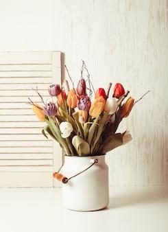 Tulipes de couleur avec des branches dans une canne blanche. décor de printemps
