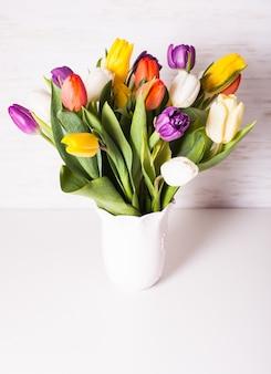 Tulipes de couleur dans un vase blanc. concept de printemps avec espace de copie