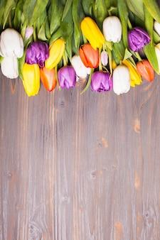Tulipes de couleur sur la planche de bois gris rustique. concept de printemps avec espace de copie
