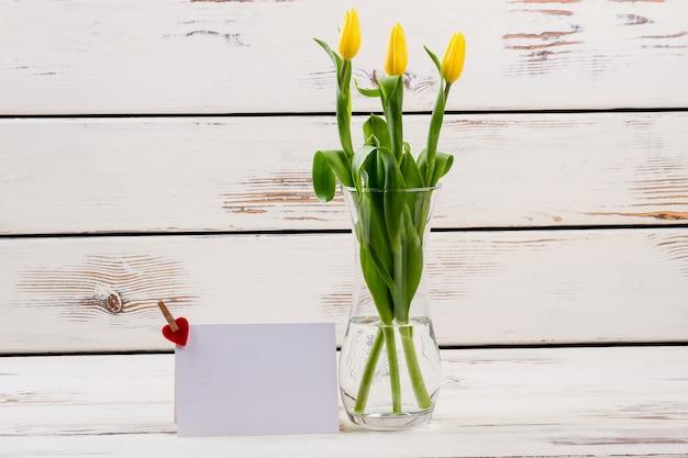 Des tulipes dans un vase près du papier cartonné avec un cœur près des fleurs partagent l'amour et la joie de l'ambiance festive tout autour