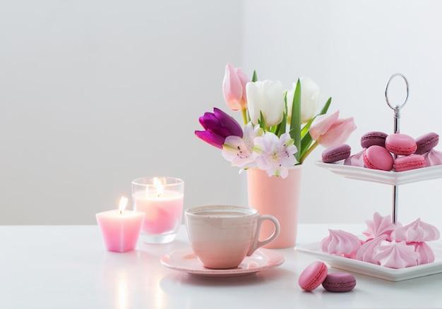 Tulipes dans un vase et une tasse de café avec dessert sur blanc