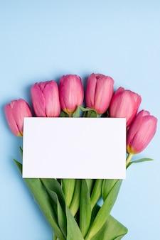 Tulipes de fleurs roses et carte présente sur une surface bleue
