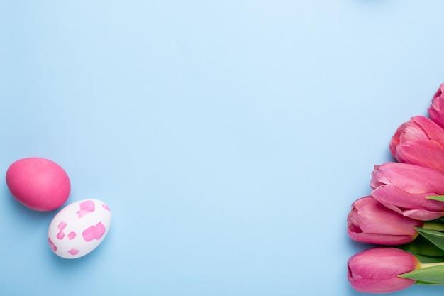 Tulipes de fleurs roses et oeufs de pâques sur une surface bleue