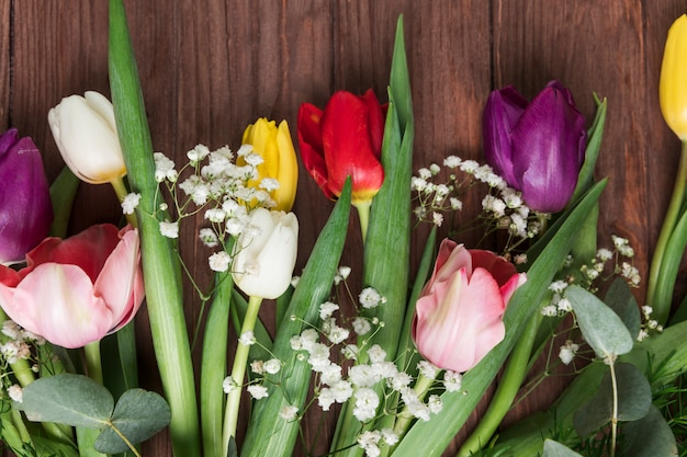 Tulipes fraîches colorées et fleur d'haleine de bébé sur le bureau en bois