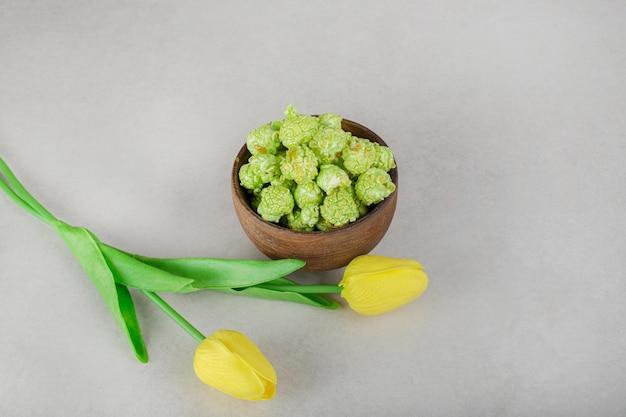 Tulipes jaunes et un bol de bonbons de maïs soufflé sur table en marbre.