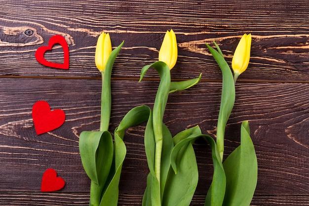 Tulipes jaunes et coeurs. fleurs près des coeurs en tissu. créez une ambiance romantique. cadeau fait avec amour.