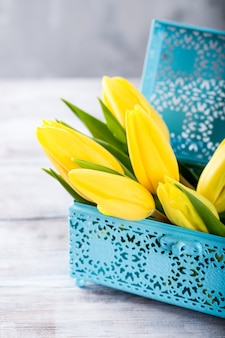 Tulipes jaunes dans une boîte en métal bleu sur la surface gris clair. un cadeau pour la journée de la femme. carte de voeux pour la fête des mères. copier l'espace