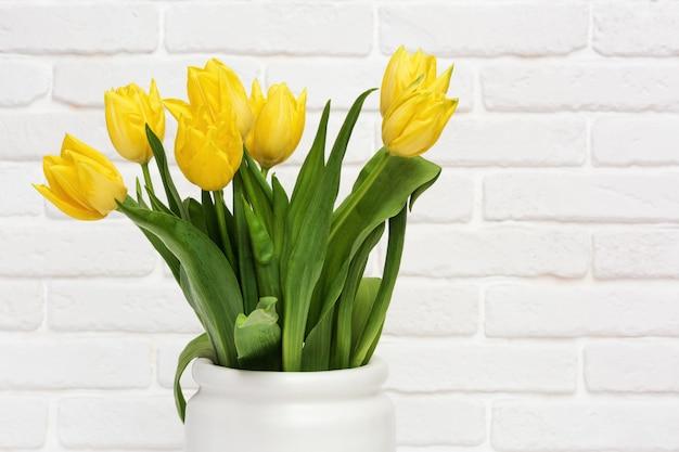 Tulipes jaunes dans un vase. fleurs de printemps au printemps sur mur de briques décoratives blanches. fleuri naturel.
