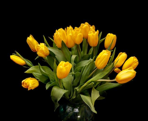 Tulipes jaunes dans un vase en verre sur fond noir. belles fleurs. la saint valentin. 8 mars. photo de haute qualité