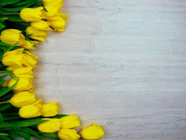 Tulipes jaunes sur l'espace de copie en bois.