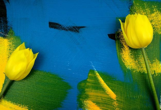 Tulipes jaunes avec des feuilles d'eucalyptus à plat sur fond acrylique abstrait fait main coloré