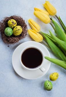 Tulipes jaunes, oeufs de caille et tasse de café noir sur fond de pierre bleue