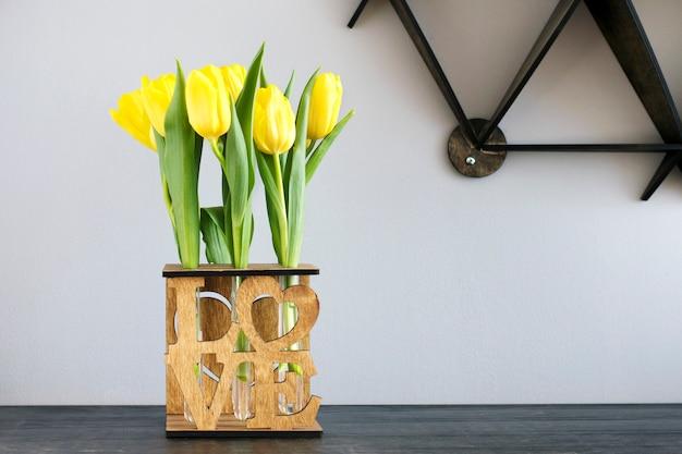 Tulipes jaunes de printemps dans un vase en bois à la mode avec des tubes à essai sur une table sur un fond gris