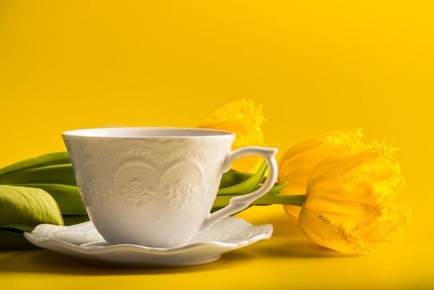 Tulipes jaunes avec une tasse de thé ou de café sur jaune