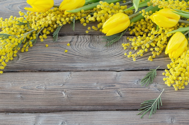 Tulipes et mimosa sur fond de bois ancien foncé