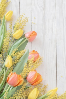 Tulipes et mimosa sur fond de bois blanc