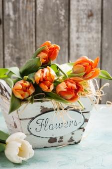 Tulipes orange dans un panier en bois sur rustique