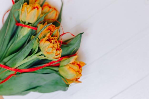 Tulipes orange sur fond en bois blanc