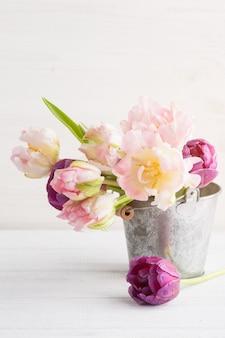 Tulipes pourpres roses dans un seau en étain