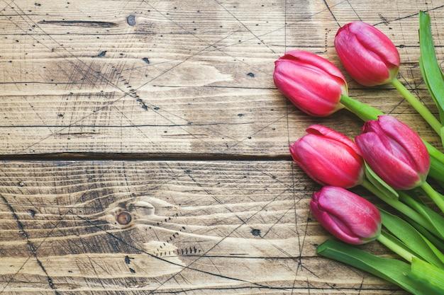 Tulipes pourpres roses sur fond en bois avec espace de copie.
