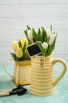 Tulipes printanières dans un vase jaune et un arrosoir