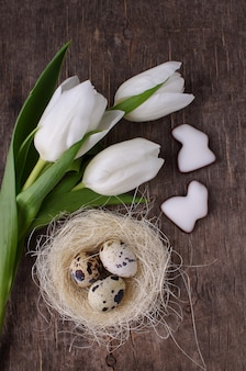 Tulipes printanières et oeufs de caille sur un vieux fond rustique, pâques