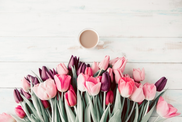 Tulipes de printemps et une tasse de café sur une table en bois blanc