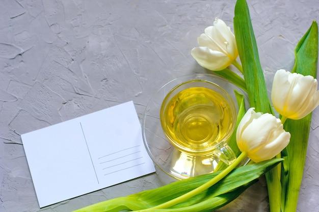 Tulipes de printemps tendres et une tasse de thé vert sur fond de ciment gris