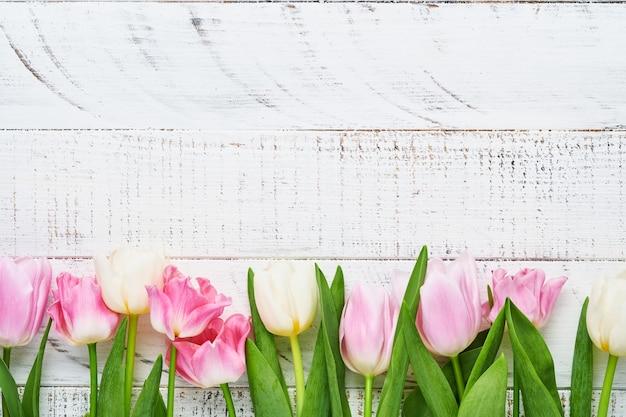 Tulipes roses et blanches sur fond de bois blanc.