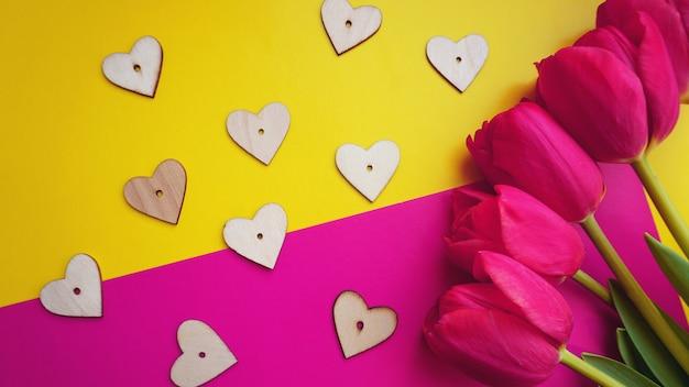 Tulipes roses avec des coeurs sur fond rose. mise à plat, vue de dessus. fond de la saint-valentin. notion de printemps.