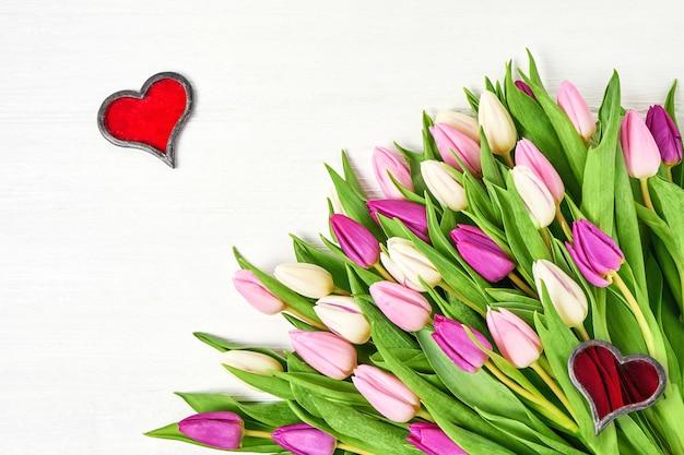 Tulipes roses avec des coeurs rouges sur un fond en bois blanc.
