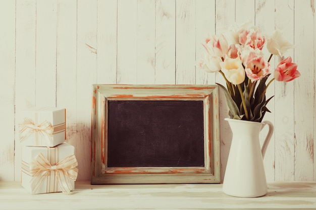 Tulipes roses en cruche et tableau en bois vert. concept de la journée des enseignants