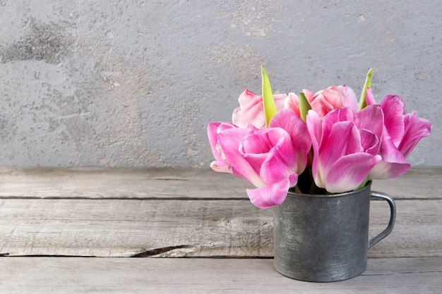 Tulipes roses dans une tasse en métal vintage