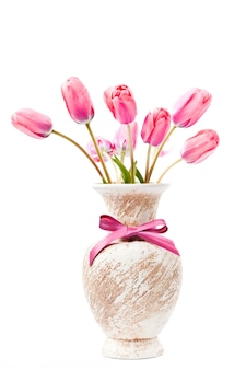 Tulipes roses dans un vase avec un arc isolé sur blanc