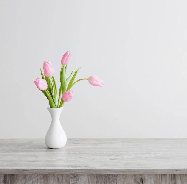 Tulipes roses dans un vase en céramique blanche sur table en bois sur fond mur blanc
