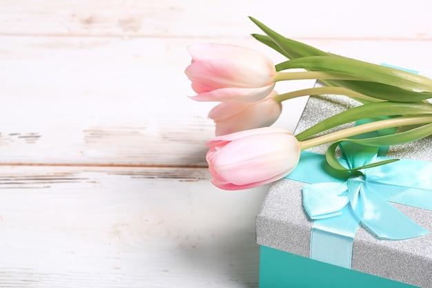 Tulipes roses délicates sur une boîte cadeau turquoise.