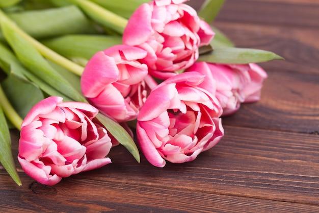 Tulipes roses délicates sur un fond en bois marron. fermer. composition de fleurs. fond de printemps floral. saint valentin, pâques, fête des mères.