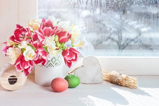Tulipes roses et fleurs de freesia blanches au bord de la fenêtre, décorations de pâques