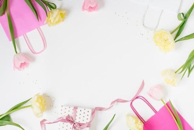 Tulipes roses et jaunes, sacs-cadeaux en papier rose vif et coffret cadeau avec espace de copie sur fond blanc