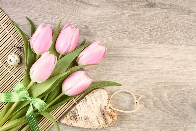Tulipes roses, oeuf de caille et coeur en bois sur table, fond pour votre texte