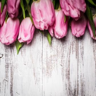 Tulipes roses sur une table en bois blanc minable